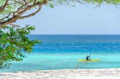Équipez monter un kayak par une plage d'Aruba Photographie stock