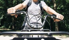 Équipez monter un vélo par un parc public Images stock