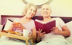 Équipez montrer à amie quelque chose sur le livre pendant le petit déjeuner Photos libres de droits