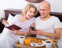 Équipez montrer à amie quelque chose sur le livre pendant le petit déjeuner Photo stock