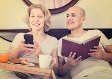 Équipez montrer à amie quelque chose sur le livre pendant le petit déjeuner Photographie stock