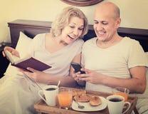 Équipez montrer à amie quelque chose sur le livre pendant le petit déjeuner Images stock