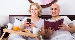 Équipez montrer à amie quelque chose sur le livre pendant le petit déjeuner Photos stock