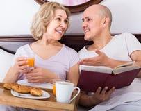 Équipez montrer à amie quelque chose sur le livre pendant le petit déjeuner Image stock