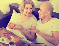 Équipez montrer à amie quelque chose sur le livre pendant le petit déjeuner Image libre de droits