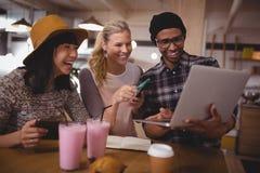 Équipez montrer l'ordinateur portable aux amis féminins gais au café Photo stock