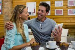 Équipez montrer le comprimé numérique à l'amie en café Image stock