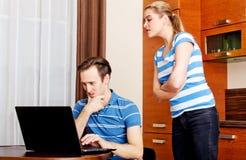 Équipez observer quelque chose sur l'ordinateur portable, son épouse essayant de regarder ce qui il faisant Image stock
