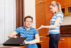 Équipez observer quelque chose sur l'ordinateur portable, son épouse est fâché Images stock