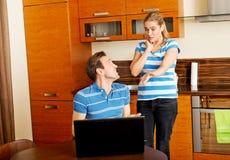 Équipez observer quelque chose sur l'ordinateur portable, son épouse est fâché Photos libres de droits