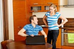 Équipez observer quelque chose sur l'ordinateur portable, son épouse est fâché Image stock