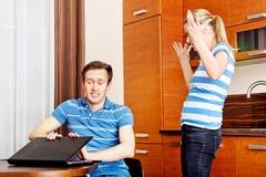Équipez observer quelque chose sur l'ordinateur portable, son épouse est fâché Image libre de droits
