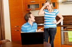Équipez observer quelque chose sur l'ordinateur portable, son épouse est fâché Photographie stock libre de droits