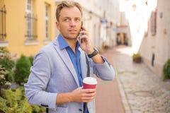 Équipez parler au téléphone avec du café dans des ses mains Images libres de droits