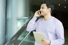 Équipez parler au téléphone et tenir le comprimé faisant des affaires photo libre de droits