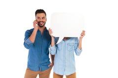 Équipez parler au téléphone, femme tient la bulle de la parole au-dessus du visage Photographie stock