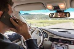Équipez parler au téléphone portable tout en conduisant ne pas prêter l'attention à la route photo stock
