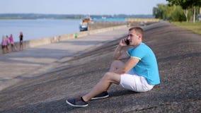 Équipez parler au téléphone près du lac banque de vidéos