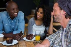 Équipez parler avec des amis à la table dans le café Images libres de droits