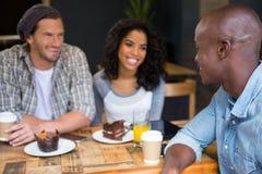 Équipez parler avec des amis à la table dans le café Photo libre de droits