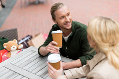 Équipez parler avec son amie tout en buvant du café jetable au café Images stock