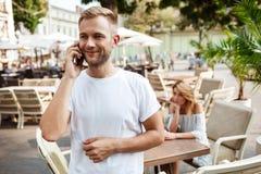 Équipez parler du téléphone tandis que son amie étant ennuyée Image libre de droits