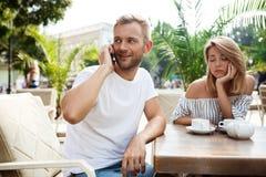 Équipez parler du téléphone tandis que son amie étant ennuyée Photos libres de droits