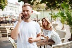 Équipez parler du téléphone tandis que son amie étant ennuyée Photo stock