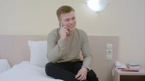 Équipez parler et rire sur son smartphone posé sur un lit Image stock
