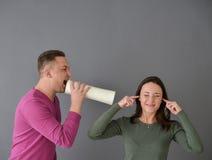 Équipez parler par le tube et une femme branchant ses oreilles Photographie stock libre de droits