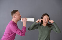 Équipez parler par le tube et une femme branchant ses oreilles Images stock