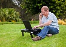 Équipez parler sur le téléphone portable devant un ordinateur portatif images stock