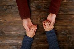 Équipez partager la vue supérieure de mains du ` s de femme sur le fond en bois Concept d'amour et de soutien Photos stock