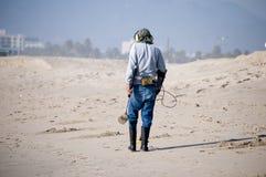 Équipez peigner la plage avec un détecteur de métaux  Images libres de droits