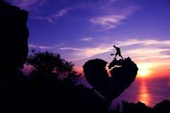 Équipez peller la pierre pour réparer la roche de forme du coeur brisé sur la montagne Photographie stock