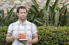 Équipez penser à l'avenir tenant un livre et une tasse orange dehors Image stock