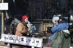 Équipez photographier son amie dans un chapeau rouge, se reposant dans un café Vue par la fenêtre d'un café Images stock