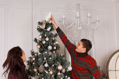 Équipez placer un ornement sur un arbre de Noël Images libres de droits