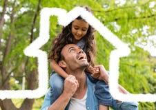 Équipez porter sa fille sur son épaule contre le contour de maison à l'arrière-plan images stock