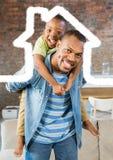 Équipez porter son fils sur son épaule contre le contour de maison à l'arrière-plan images libres de droits