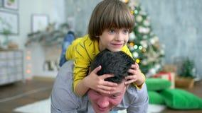 Équipez porter son fils très mignon sur le sien dos à la maison Père heureux et petit garçon ayant l'amusement sur le fond de joy banque de vidéos