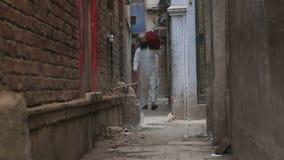 Équipez porter un sac par un passage étroit à Varanasi banque de vidéos