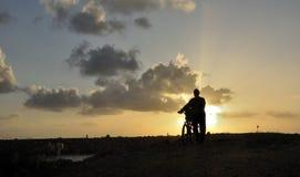 Équipez pousser son vélo avec le sien de nouveau au coucher de soleil Photos stock