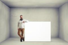 Équipez près de l'affiche énorme dans la chambre avec les murs blancs Image libre de droits