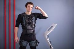 Équipez près de la machine de SME, stimulation de muscle, montrant le biceps Photographie stock