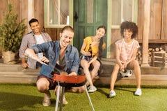 Équipez préparer le gril de barbecue sur le patio tandis que ses amis s'asseyant au porche Photo libre de droits