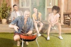 Équipez préparer le gril de barbecue sur le patio tandis que ses amis s'asseyant au porche Image libre de droits