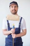 Équipez prêt à peindre un mur tenant des outils de peinture Image libre de droits