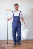 Équipez prêt à peindre un mur tenant l'outil de peinture Photos libres de droits