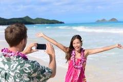 Équipez prendre des photos avec le smartphone de la femme de plage Photo stock